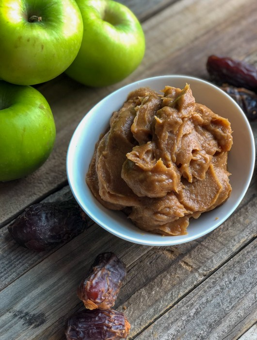 Healthier date caramel in a bowl with granny smith apples and dates around it