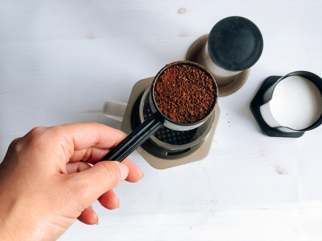 Scooping coffee beans into aeropress