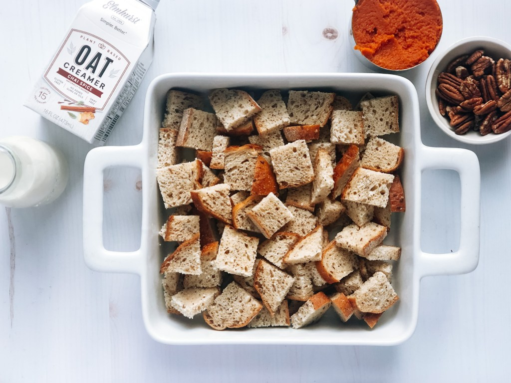 Bread cubes in baking tray with chai oat creamer and canned pumpkin on the side