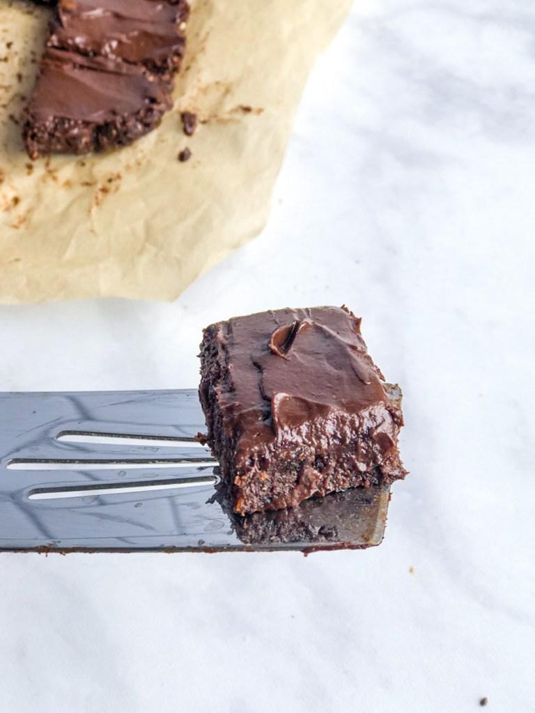 Raw vegan brownie with avocado frosting on a spatula