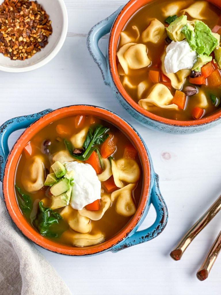 Bowl of healthy vegetarian black bean soup with tortellini topped with avocado and greek yogurt