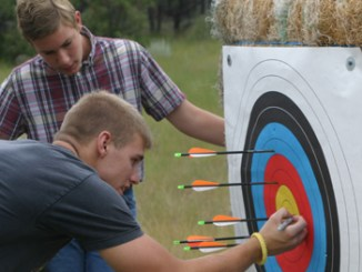 Mason Scritchfield watches as Trenton Schindler checks his score during Saturday's archery competition.
