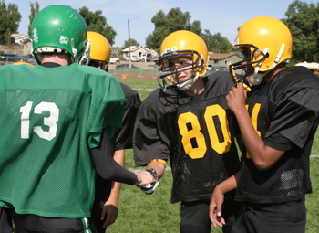 Meeker's Justin Giao and other Cowboy captains shake hands with their Rangely counterparts before the beginning of Saturday's A-team game. Meeker prevailed over its county rival, 14-12.