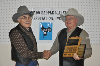 Bob Klenda, left, president of the CSMA, presents the Munsell Award to Mike Brennan. Both Klenda and Brennan are saddle makers from Meeker.