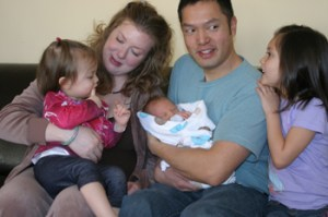 Amy Que, holding her daughter Evangeline, has had two home births during the time the Ques have lived in Meeker. Husband Michael holds Samuel, who was born the day after Christmas. Oldest daughter Charlotte, far right, was born in a hospital in Nebraska, where home births are illegal using a midwife.