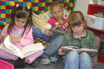 Meeker kindergarten students, from left, Devany Gaeta, Nevaeh Rowles and Melody Marquette looked at books last Friday.