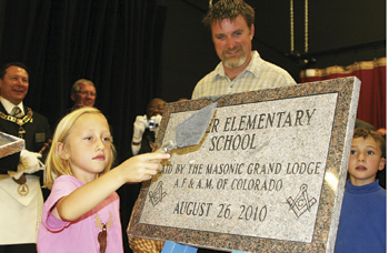 JEFF BURKHEAD Sophia Goedert, along with fellow student Josh Day, was chosen to participate in the Aug. 26 cornerstone ceremony at the new Meeker Elementary School. Standing behind the cornerstone is Jason Hightower, principal. Masons from Rio Blanco County and other parts of Colorado conducted the dedication ceremony.