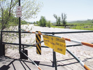 """The Meeker Circle Park gate has been locked for several days, closing the bridge and access to the park because of high water. The annual """"Fishing is Fun"""" day, sponsored by the Colorado Division of Wildlife and several local businesses, was canceled Saturday and the CDOW is tentatively rescheduling for June 25. The water was running at 5,920 cfs yesterday and there is still a lot of snow in the high country."""