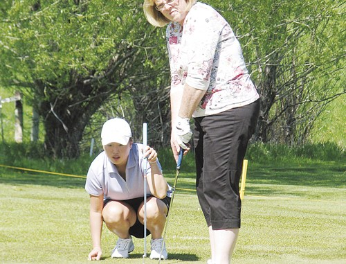 Amanda Back (above left) helps her mother Sherry Rubin line up a putt during the annual Ladies Deerfly tournament held last Saturday at the Meeker Golf Course. The mother/daughter team proved to be the best golfers on the course, winning the first flight.