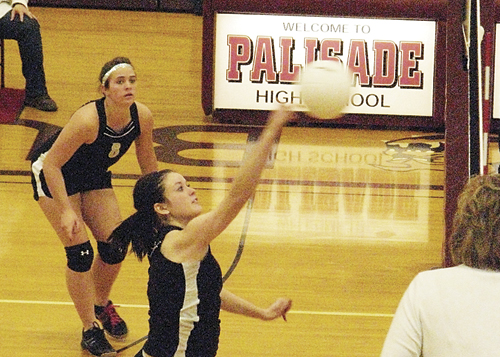 Meeker senior Katie Morgan spikes a ball as classmate Kathryn Doll prepares for a return. Morgan, Doll and classmates Aubrey Walsh and Adrienne Wix played their final matches of their high school careers in the regional tournament last Saturday in Palisade.