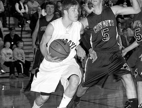 Cowboy senior Trey Morris maneuvers under the basket between the baseline and a Plateau Valley defender. Morris scored 13 points in the 59-42 Cowboy victory and scored 20 in Paonia, where the Cowboys won 67-63. Meeker will host Vail Mountain Friday and travel to play their Rio Blanco County rival in Rangely Saturday.