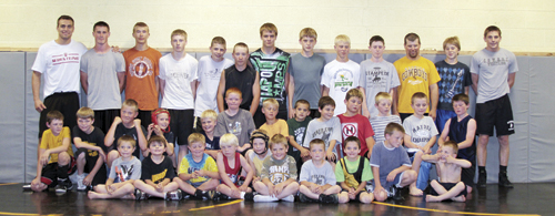 (Above) Four-time NCAA Division I All-American Joe LeBlanc (top left) and former University of Wyoming teammate Brandan Richardson (top right) held a clinic for more than 30 wrestlers from Meeker and Rangely last Thursday in Meeker's wrestling room. (Bottom right) LeBlanc and Meeker head coach J.C. Watt watch as wrestlers practice LeBlanc's technique.