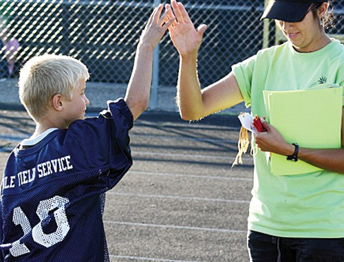 courtesy photo Kelton Turner gets a high five from Nicole Dupire after winning the annual Punt, Pass and Kick competition recently held and will be advancing with other winners to the Sectional competition in Grand Junction.