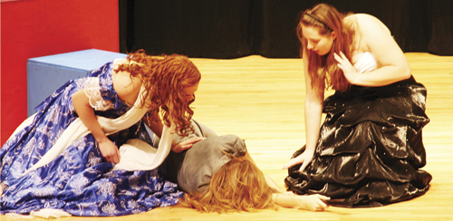 Marie (Chelsea Ficken, left) and Giselle (Kymberlie Hemphill) try to revive Madame Pompadour (Leslie Hernandez) after threats made by the mysterious Phantom of the Opera.