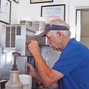"Bill Mitchem mixes the 1,000th milk shake this summer at the BedRock Depot at Dinosaur, called an ""oasis"" and a favorite by travelers along Highway 40."
