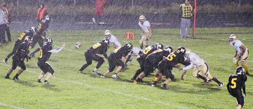 Cowboy quarterback Jake Phelan prepares to receive a snap in the snow during the game against the Lake County Panthers, which Meeker won 46-0. Phelan led the team with 111 yards rushing, 66 passing and an interception on defense.