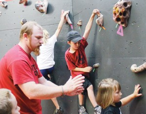 John Whipple, this year's College For Kids Climbing Course instructor and Colorado Northwestern Community College's Outdoor Leadership Program coordinator, taught 17 children about stretching, climbing techniques and safety at CNCC's climbing gym last week. Above, Whipple instructs students on technique while showing the standing children how to spot climbers overhead. Forty-five children filled all but one CNCC College For Kids class this year, said Angie Miller, CNCC's community education coordinator and the program's organizer. Miller said participation in College For Kids has climbed steadily since the program returned several years ago, and she attributed much of its success to instructors, parents and children bringing their enthusiasm and involvement to the courses.