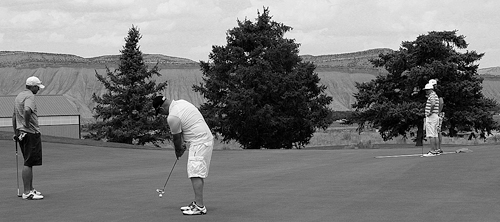 Rangely's Ryan Kennedy watches his partner Jason Cox putt, while Chris Hejl and his partner Keenan Harvey await their turn. Hejl and Harvey had the best score in the third flight and Kennedy and Cox had the second best net score in the same flight of the 27-hole, two-man tournament played at Cedar Ridges.