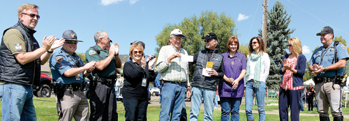 "Eddie O'Brien, the community liaison for The Colorado Grand, presented a couple of checks Sept. 11 as the charitable organization's vintage sports cars rolled through town, with a stop at City Park, which included lunch served by the Meeker Lions Club. ""We've been coming to Meeker for at least a half dozen times. We put on this event once a year. It's a four-day event that runs through the state of Colorado,"" O'Brien said. ""We raise a lot of money. We'll give away between $300,000 and $400,000 per year to all of the communities we go through."" O'Brien presented checks for $7,500 to the Meeker Lions Club and a $7,500 check for a local student going to a college or university in Colorado. Paul Jordan and Julie Pearce accepted on behalf of the Meeker Lions Club."