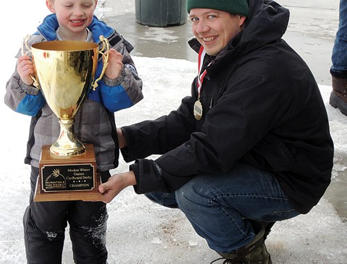 The overall winner of the race event at Paintbrush Park on Saturday was Xavier Buisker, left, who is assisted in holding his winning trophy by his father, Adam. The entire Buisker family participated, and Xavier's sister, Lilly, won a ribbon as well. As soon as the races were over, free hot dogs and hamburgers were served to the participants by Bobby Gutierrez of Wendll's/Cuppa Joe.