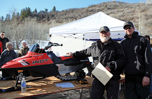 "Mike Sizemore, left, presents the grand prize of a Polaris 120 child's snowmobile  from the ""I Ride With James"" snowmobile and poker run on Sunday to Luke Weeldreyer of Craig. First place and $1,000 went to Cole Steiner, second place and $500 went to Chris King, and third place and $250 went to Deb Overton. More than 100 riders took part in the ride and poker run despite a lack of snow at the base camp at  Lost Creek Trailhead. The event is in memory of Mike and Kathy Sizemore's son, James, who was killed Feb. 20, 2011, in an avalanche on nearby Sand Peak."