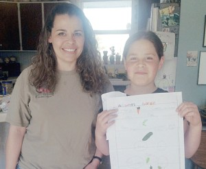 Laurie Baker and her daughter Adywen Meeks, 9, show the garden plan that Meeks created to plan out fruit and vegetable spacing for her garden plot this year. Meeks, who began with a children's garden plot last summer, is graduating to a full-sized plot this gardening season.