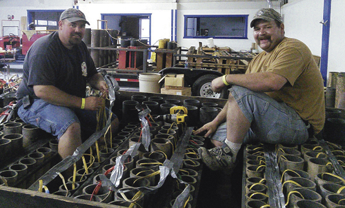 Certified pyro-technicians Zack Allen, left, and Rich Merriam, right, load three-, four- and five-inch tubes with fireworks shells on the main show trailer and wire them together in preparation for the Fourth of July show.