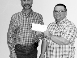 Chevron representative and Meeker resident Chris Archuleta presents a $10,000 check to Meeker Board of Education President Bill deVergie Oct. 7 for math and science programs.