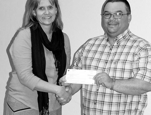 Chevron representative Chris Archuleta, a Meeker resident and school parent, presents Meeker High School Principal Amy Chinn with a $250 check for the high school FFA program.