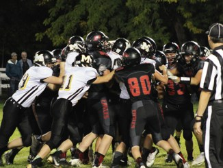 """One Meeker fan described the football game between the Cowboys and the Paonia Eagles as a """"heavyweight boxing match"""" with both teams standing toe-to-toe and exchanging punches and pictured action looked like a rugby scrum. In the middle of the scrum was T.J. Shelton who was pushed across the goal line by his teammates. Although the two-time defending state champion Eagles could not knock out the Cowboys, they did win the game 34-30. Meeker will host the Cedaredge Bruins Friday in Starbuck Stadium."""