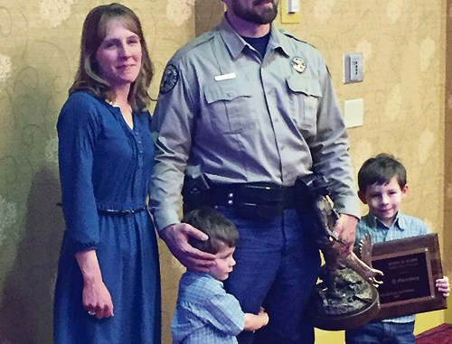 Colorado Parks and Wildlife (CPW) Area Wildlife Manager (AWM) and former Rangely resident Ty Petersburg accepts the John D. Hart Wildlife Officer of the Year Award on Feb. 24 in Colorado Springs. Wife Stephanie Petersburg and sons Lucas, 4, and Boden, 7, joined him in accepting the honor. Petersbug's parents, Donna and Steve, still live in Rangely.