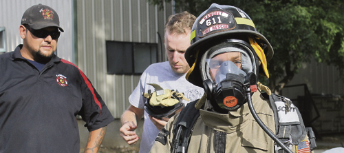 Members of the Rangely Fire and Rescue Department gave a series of demonstrations recently regarding departmental operations. Above, a couple of firemen demonstrated their working outfit by getting Luis Quintana to dress in full gear.
