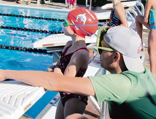 Meeker Marlin swimmer Brooklynn Nielsen gets some instruction from coach Chance Walker immediately before winning the 25-yard backstroke at the High Country Swim League Championship Meet in Eagle on July 29.