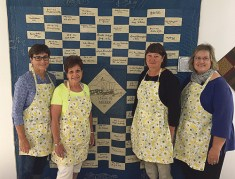 Meeker P.E.O. members hosted the sixth annual quilt show downtown. From left, Stephanie Oldland, Beverly Steinman, Peggy Shults and Sherry Overton with an antique quilt that has the names of some of Meeker's earliest pioneers. Pat Turner