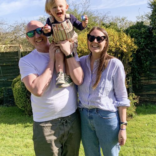 Mum, Dad and Toddler posing for a family picture in a garden.