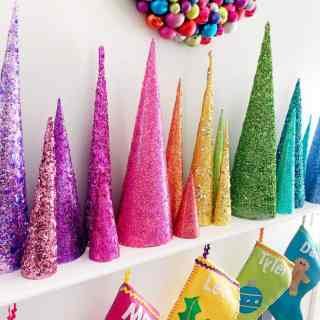 rainbow christmas tree cones with rainbow stockings and colorful ornament wreath