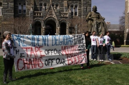 Plan A members stood chained to the statue of John Carroll as other members of the group held a banner protesting Georgetown's approach to reproductive rights.