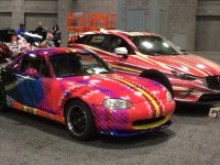 """Professor L. Collier Hyams' """"Sassy Lassie"""" tartan Mazda Miata and Zack Engler's (COL '18) """"Hyper"""" CX-3 Mazda during the Washington Auto Show setup on Wednesday, Jan. 20. The show highlights artwork from 11 Georgetown students and Hyams."""
