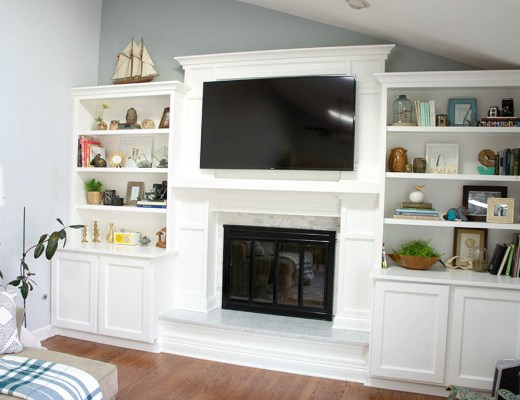 Fireplace built-ins and marble surround, TV mounted over fireplace.