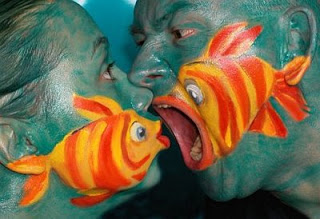 People with fish painted on their faces looking fishy.