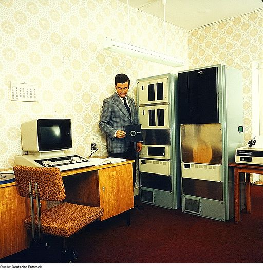 old computer and man holding a floppy disk