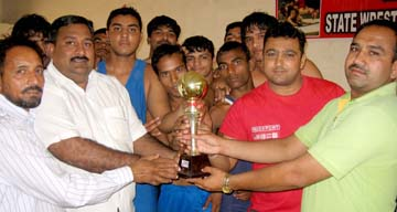 DAV College wrestlers receiving team trophy in the Senior Chandigarh State Wrestling Championship on Sunday.