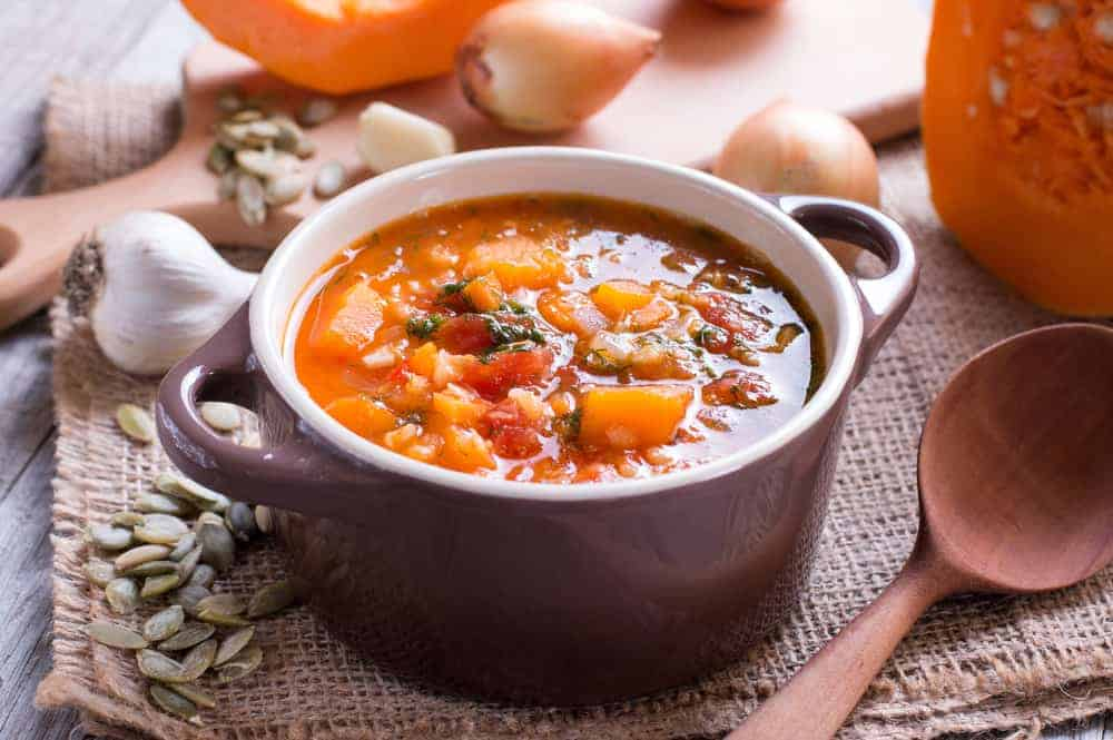 Pumpkin soup with lentils on a wooden table