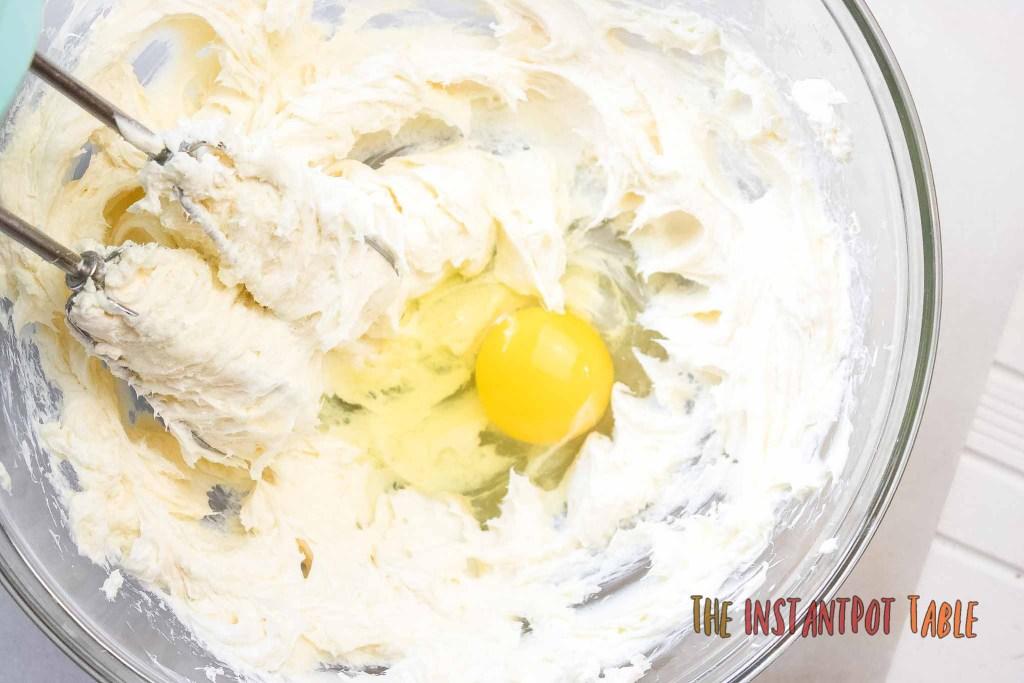 adding egg to a bowl to make cheesecake mixture