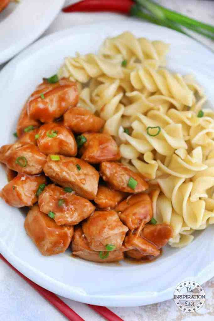 bourbon chicken and pasta on a white plate