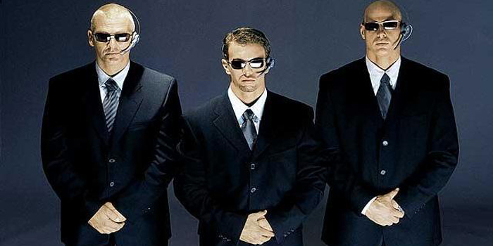 Three bodyguards in suits and sunglasses