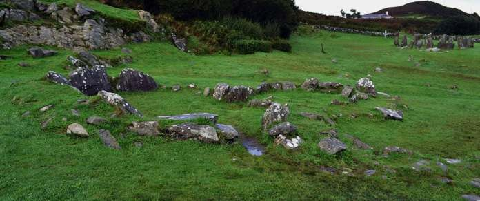The remains of the joined stone huts with the Drombeg Stone Circle upper right - The Irish Place
