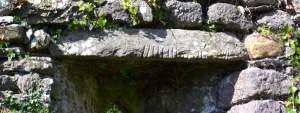 Ogham Stone used as lintel in lower window in Western Gable wall - The Irish Place