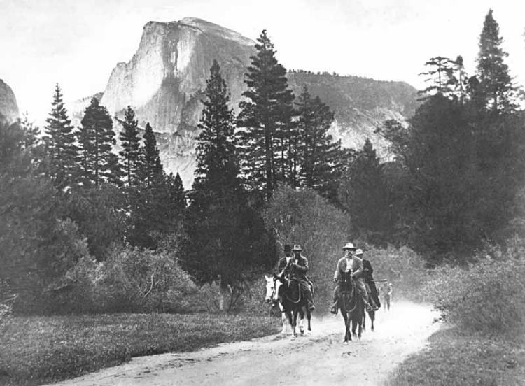 President Theodore Roosevelt and John Muir riding horses along a road in Yosemite Valley, with Half Dome in the distance, accompanied by Park Rangers Archie Leonard and Charles Leidig, followed by unidentified man on foot; left to right, Leonard, Muir, Roosevelt, Leidig.
