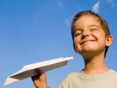 a smiling boy with a paper aeroplane toy